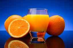 glass of Orange juice and oranges on red background