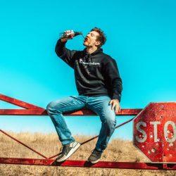 man sitting on metal fence drinking soda