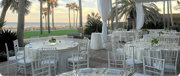 white chivari chairs and white draping by the beach wedding reception