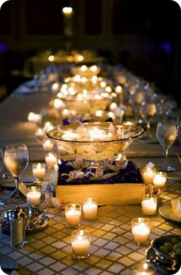 Votives placed casually around raised centerpieces consisting of floating candles in glass bowls.