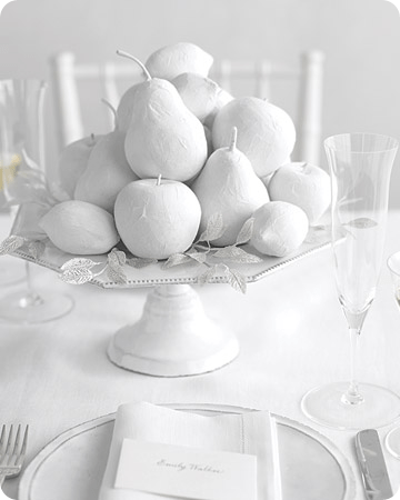 White painted fruit with silver millinery leaves sits atop of a ceramic white cake stand for a monochromatic look;