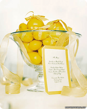 Delicious and bright yellow lemons and grapefruit centerpiece piled high with organza ribbon showcases the event menu;