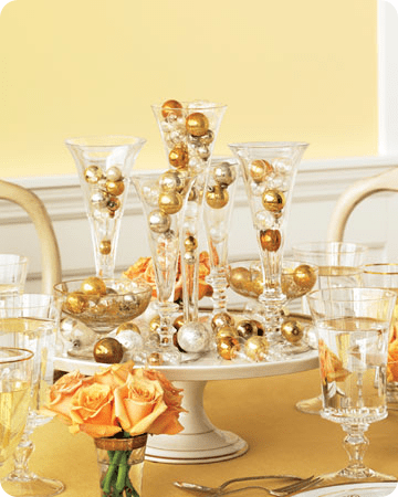 Glass flutes filled with small golden ornaments in various shades to mimic champagne bubbles