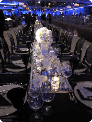 white flowers with black linens and black ghost chairs