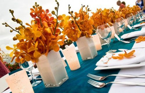 flame orange and red orchid centerpieces on estate tables