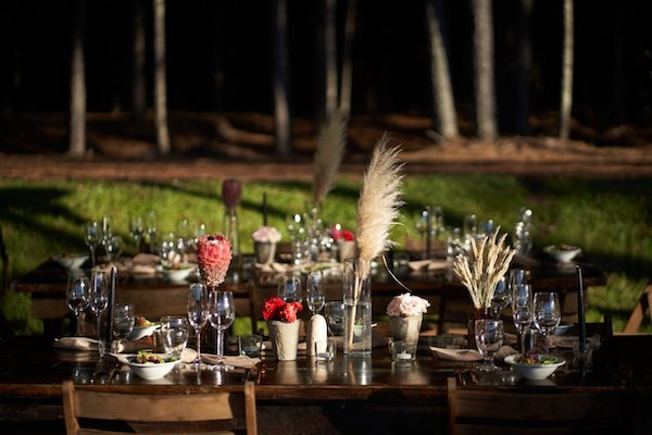 wooden farm table set with rustic grasses and floral arrangements