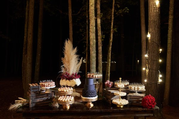 black wedding cake and desserts sitting on a wooden farm table