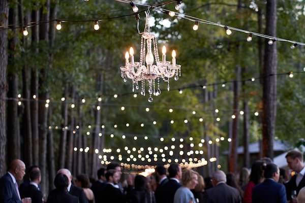 wedding guests wearing formalwear gathering in the woods under crystal chandeliers