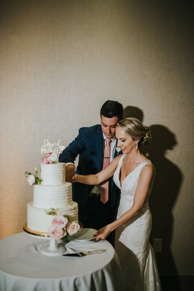 bride and groom cutting their three-tiered white wedding cake decorated with pink roses