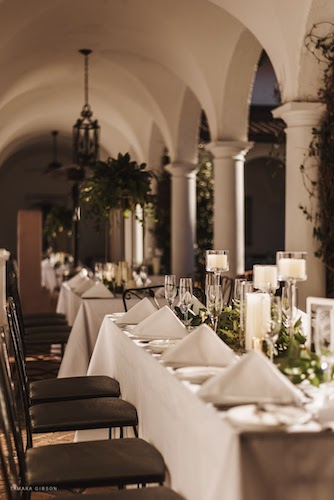 long white reception tables with lush greenery in the courtyard at Crane Cottage Jekyll Island