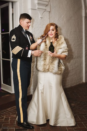 Military groom assisting his new bride in opening a champagne bottle with a saber