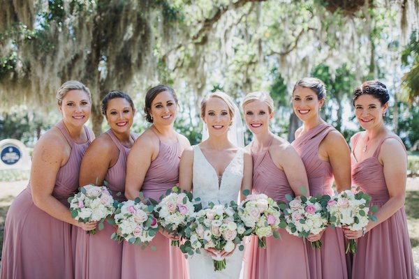 Jekyll Island bride with her bridal party wearing dusty rose bridesmaid's dresses carrying pink and white bouquets