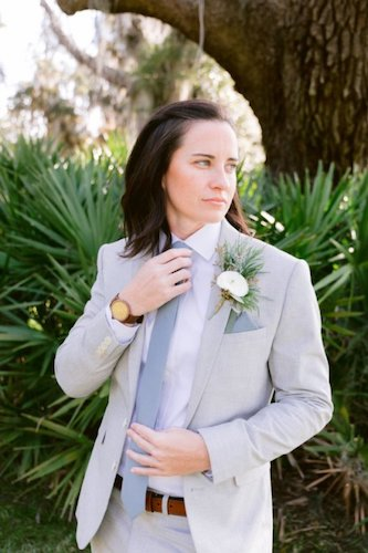 bride wearing a light blue grey suit with necktie and a white boutonniere