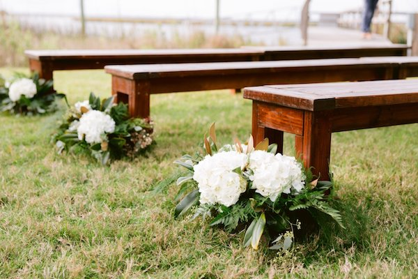 wooden benches and white aisle decor at a rustic outdoor wedding ceremony at Captain's Bluff in Saint Simons Island