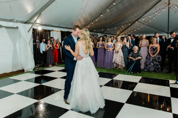 bride and groom dancing their first dance on a black and white checkered dance floor