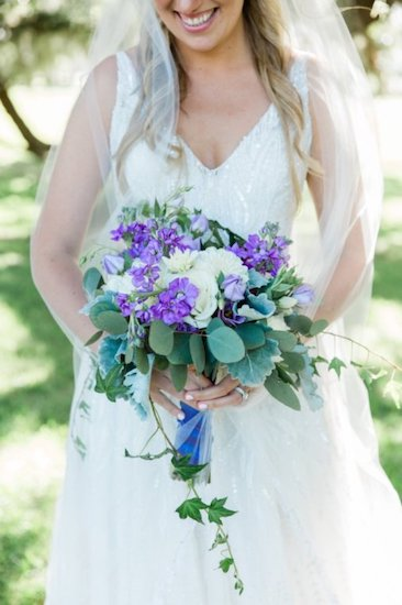 bride carrying a purple and white bridal bouquet