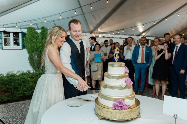 bride and groom cutting their four-tiered white and gold wedding cake at Crane Cottage