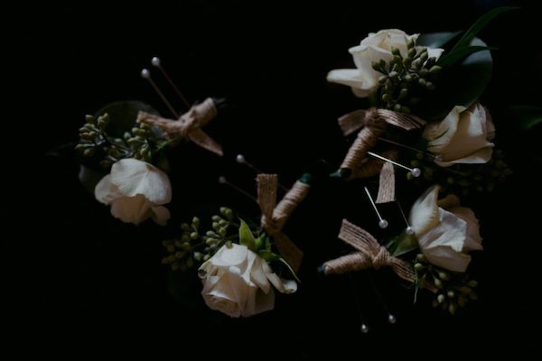 white rose boutonnieres with seeded eucalyptus and a rustic ribbon