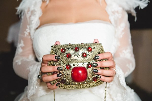 bride carrying a gold and jeweled clutch