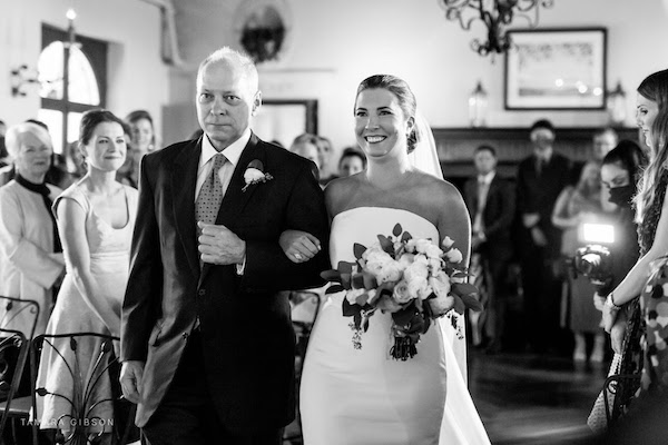 smiling bride as she walks down the aisle to her groom despite the ceremony moving indoors
