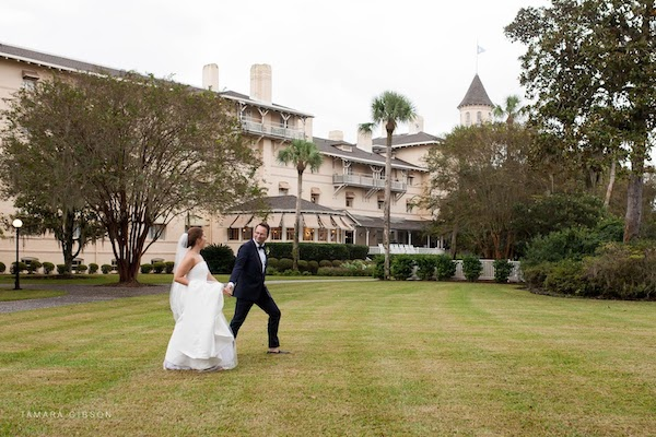 Newly married bride and groom walking across the lawn at the Jekyll Island Club