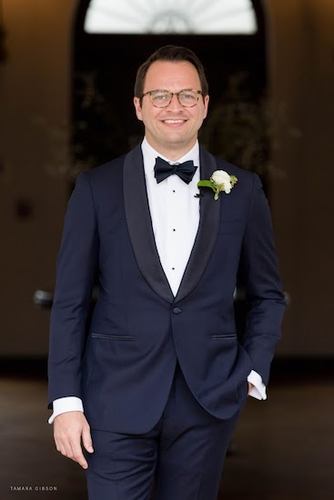 handsome groom wearing a classic tuxedo with a shawl collar and bow tie