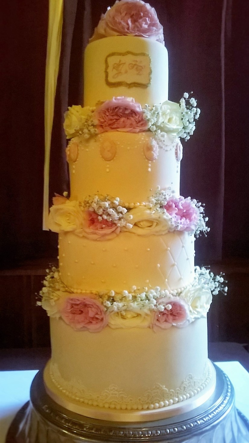Vintage cream wedding cake with fresh flowers