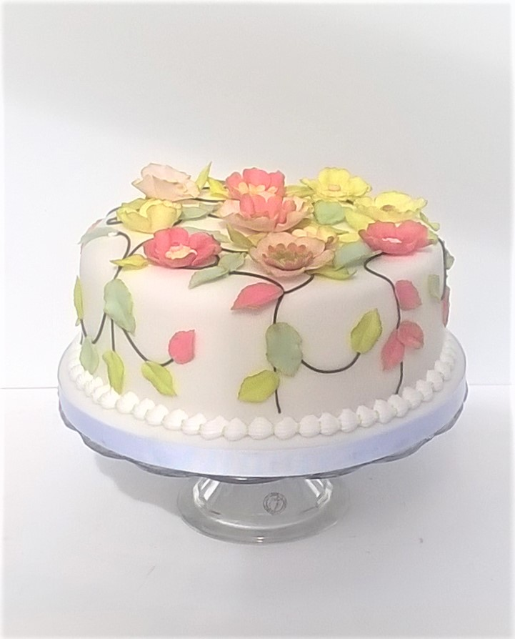 White party cake with pastel coloured fantasy flowers and leaves