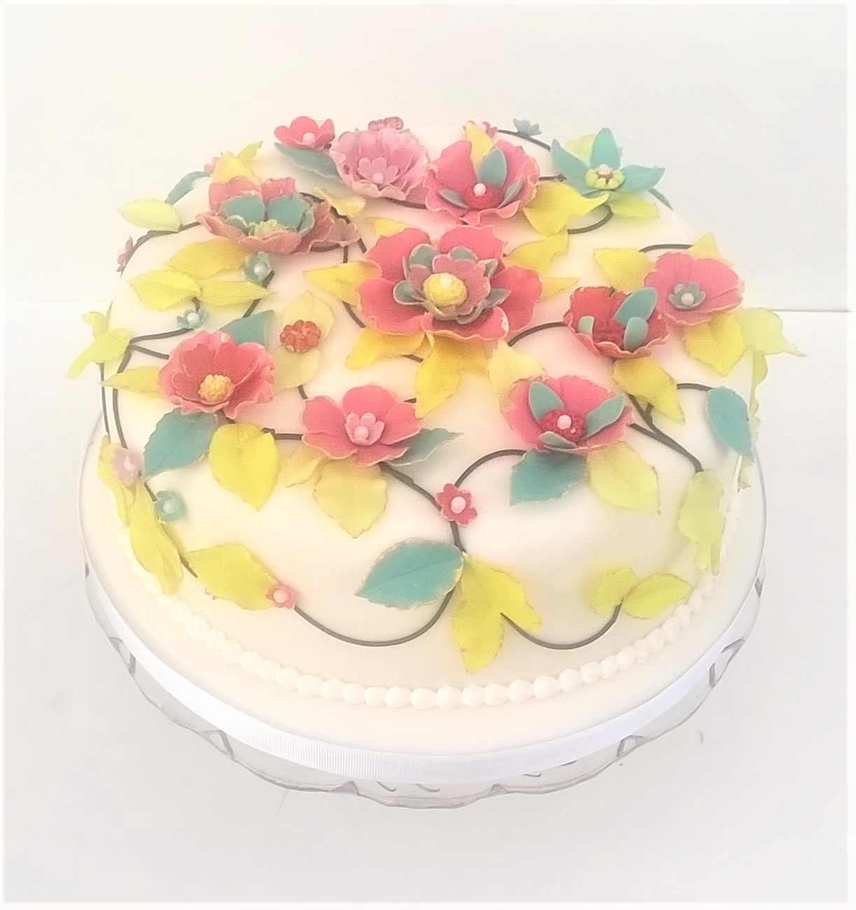 White party cake with fantasy flowers and leaves