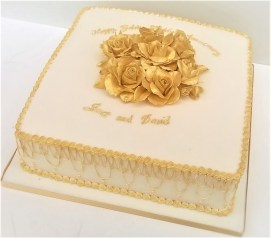 White anniversary party cake with gold roses and piping