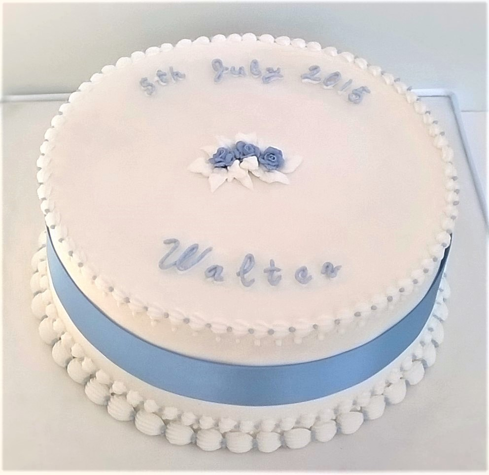 White royal iced christening party cake with piped roses