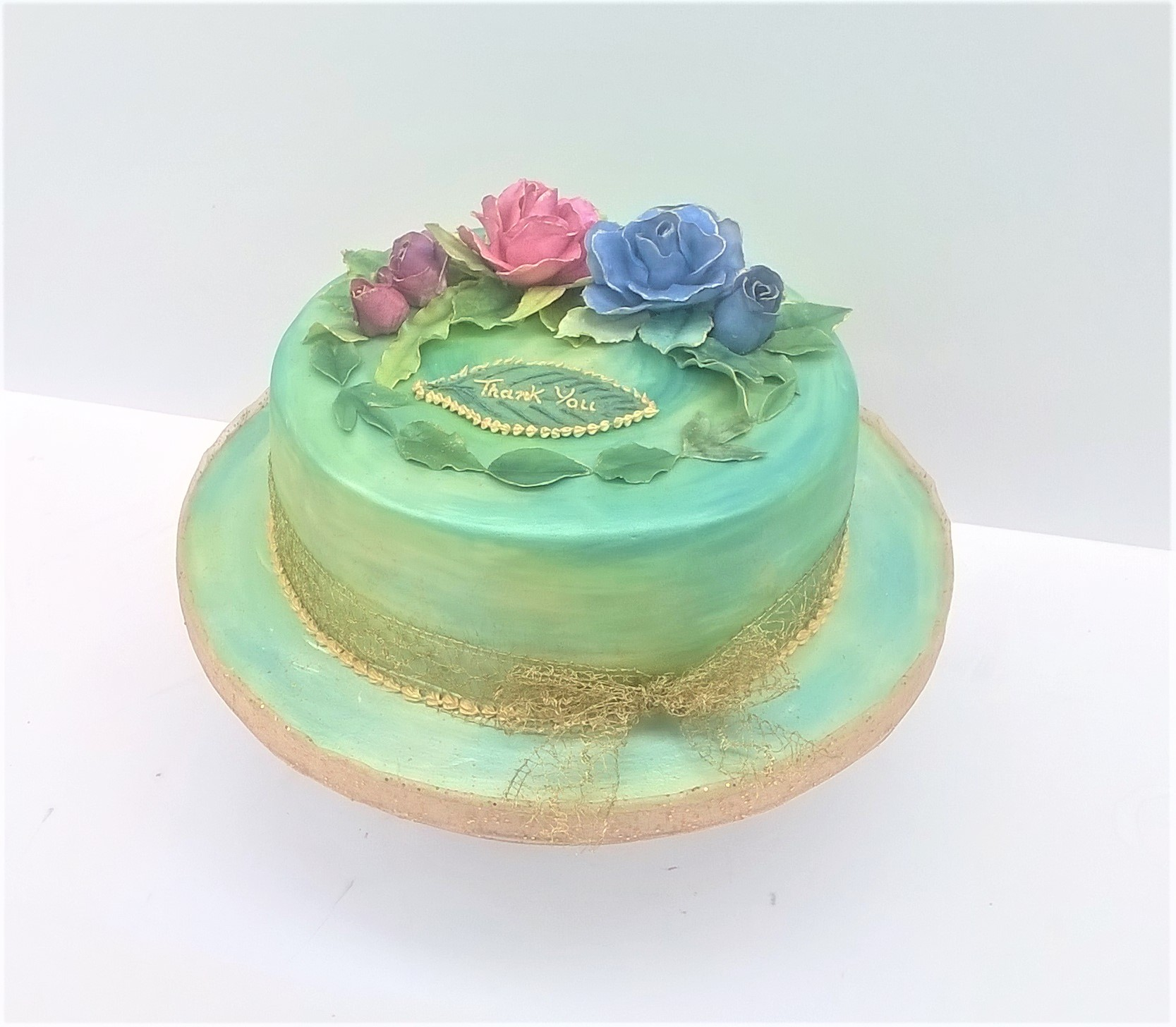 Green and gold watercolour party cake with sugar roses