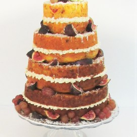 Photograph of a savoury wedding cake by Cocoa & Whey Cakes in Hampshire decorated with fresh figs and roses