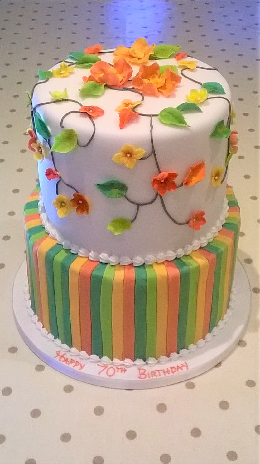 Tiered party cake with stripes and sugar flowers