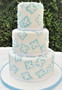 3 tier white wedding cake with blue embroidered flowers
