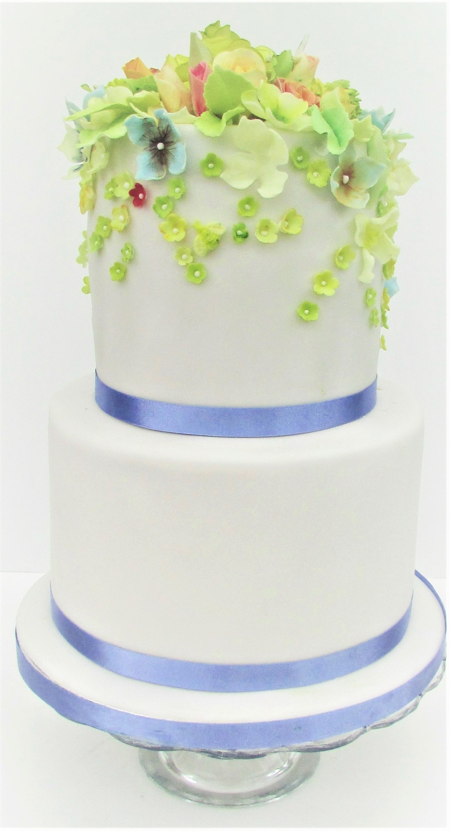 2 tier white wedding cake with sugar blossoms and purple ribbons