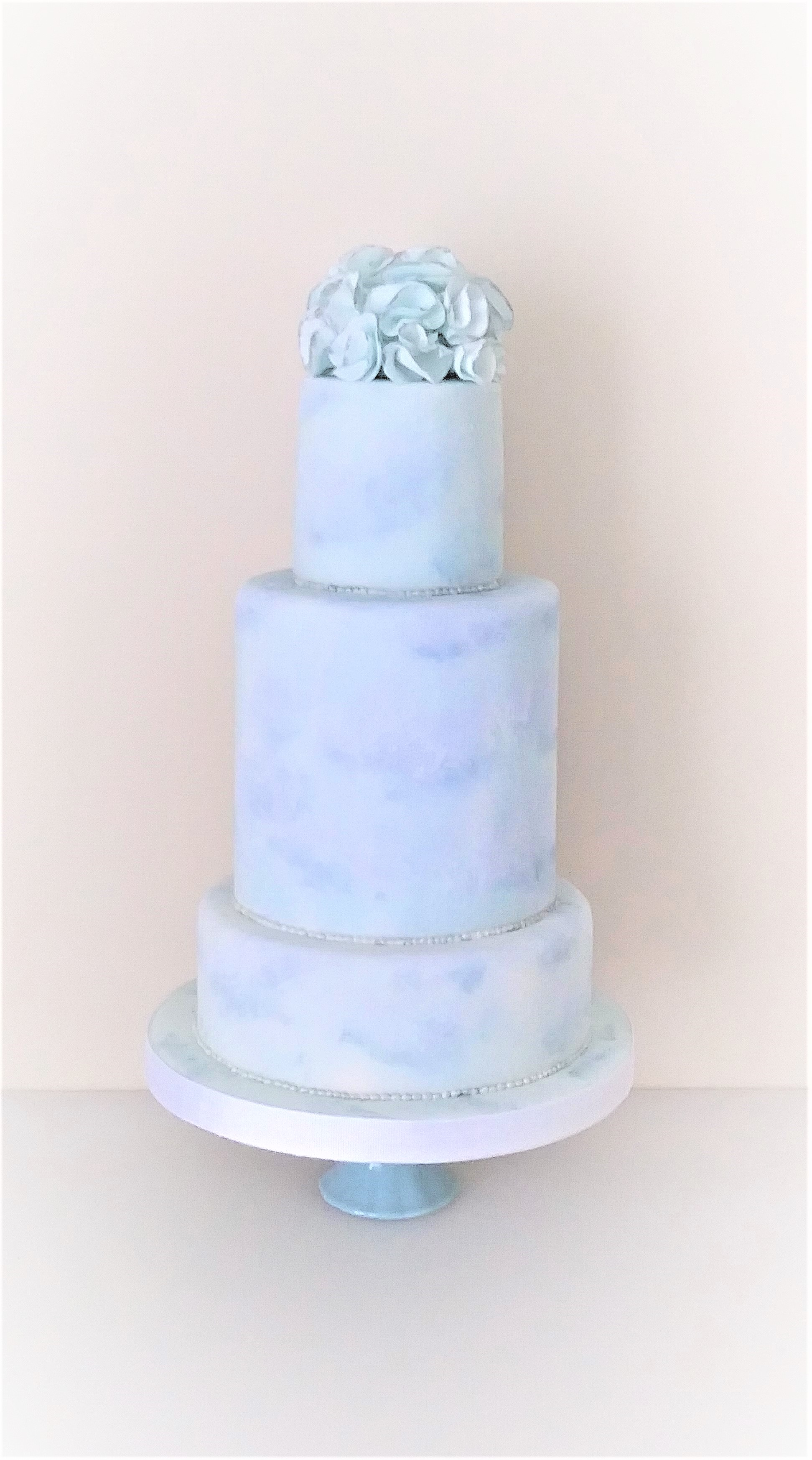 Photo of a 3 tier stacked wedding cake painted with clouds in a pale blue sky