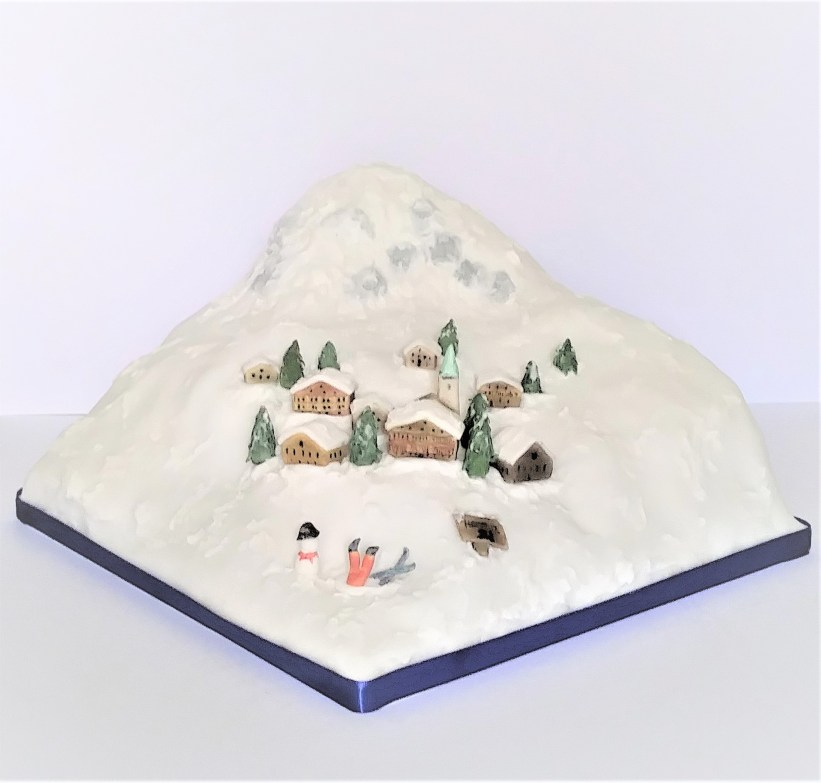 Photo of a party cake showing a snowy scene with mountains, Alpine chalets, fir trees and snowman
