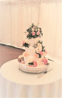 3 tier iced white wedding cake covered with beautiful fresh roses and foliage in pinks and creams