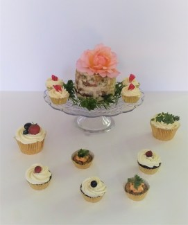 A selection of sweet and savoury cupcakes surrounding a mini savoury cheese cake