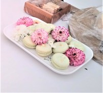 Photograph of an oblong dish of pistachio macarons decorated with gold flecks and edible flowers