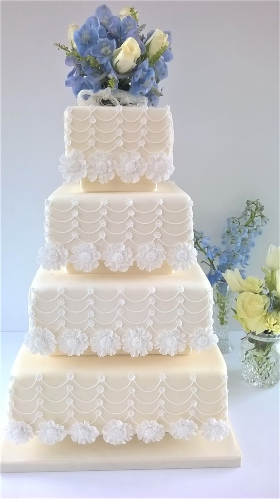 Cream & White Flower & Swags Wedding Cake by Cocoa & Whey Cakes in Dorset