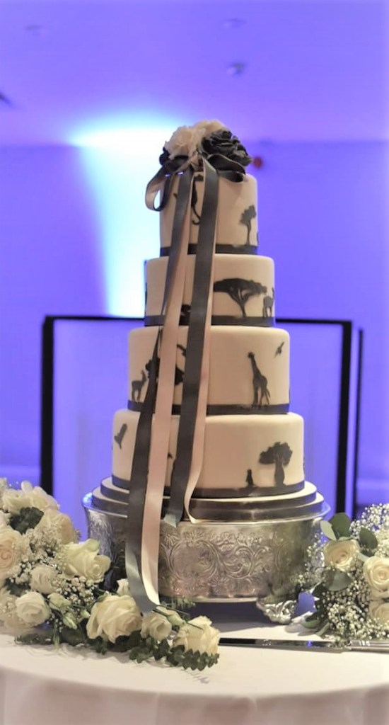 Safari Silhouette Wedding Cake with Ivory & Charcoal Roses & Ribbons by Cocoa & Whey Cakes in Dorset