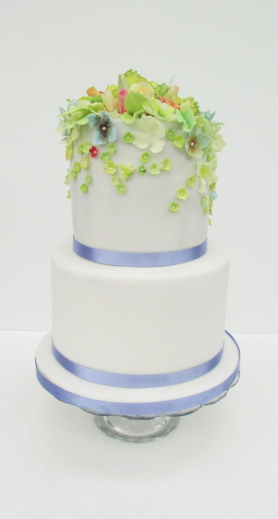 2 tier white wedding cake with sugar blossoms and purple ribbons by Cocoa & Whey Cakes