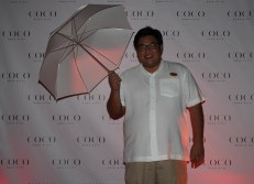 Lifestyle Associate Weijei in front of the official Coco Bodu Hithi photo backdrop