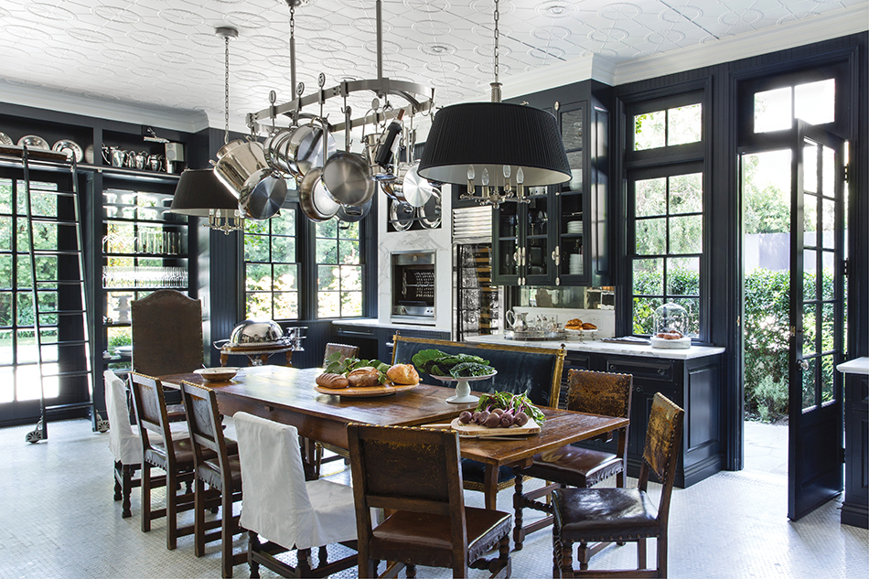 Kitchen center island with white ceiling, center island with pot rack hanging above, dark wood wall trim, and windows surrounding kitchen.