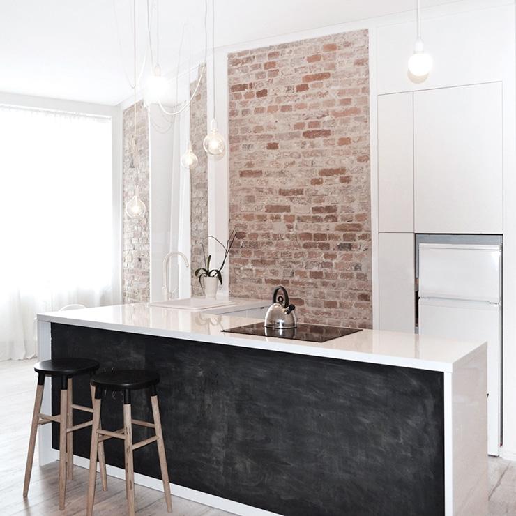 chalkboard kitchen island exposed brick waterfall counter