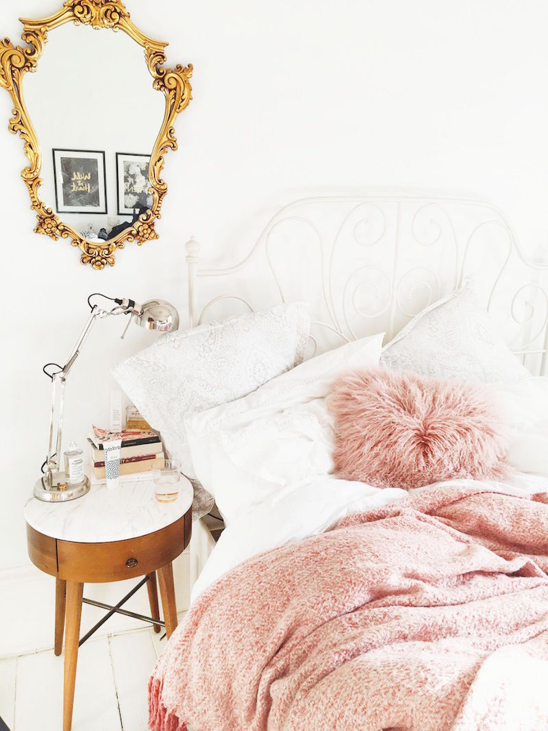 romantic bed blush blanket gold accents marble topped table