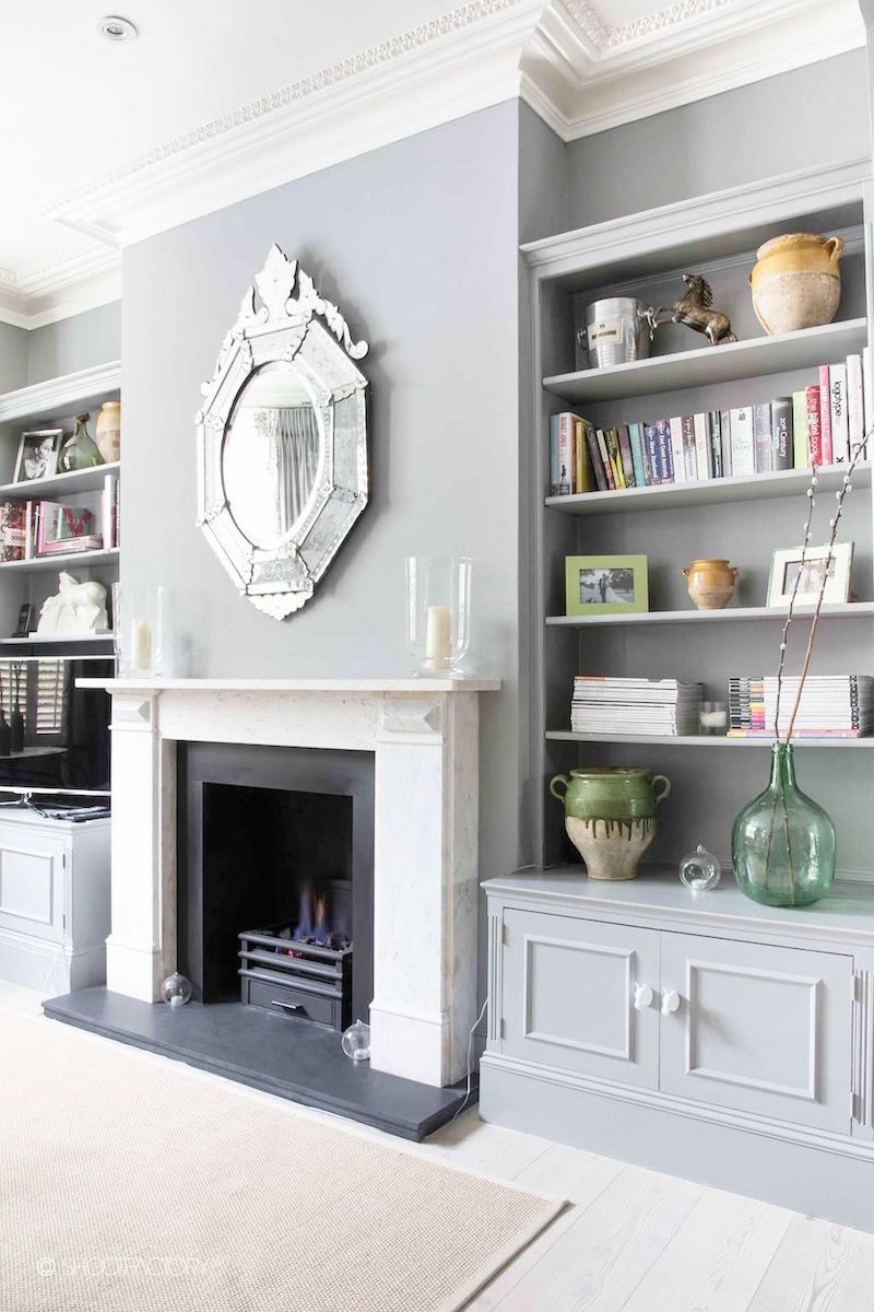 grey matte built in bookshelves ornate mirror over fireplace