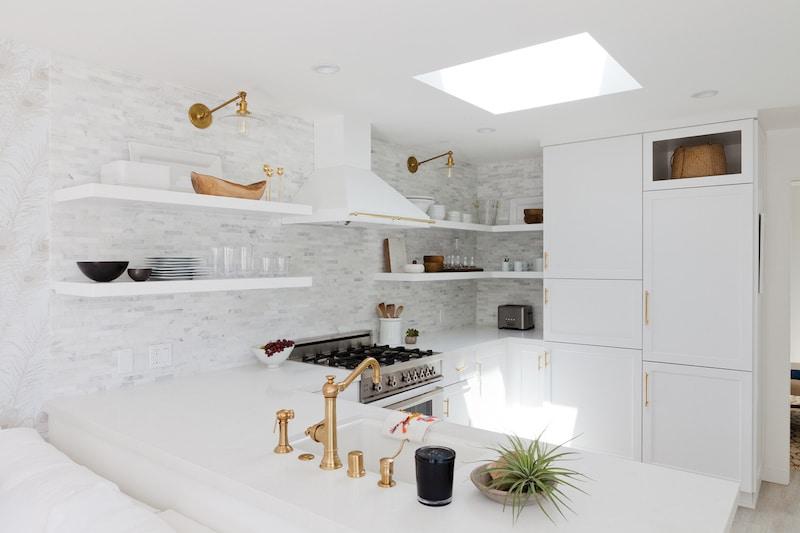 small white kitchen sky light open shelving gold fixtures